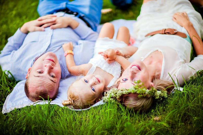 一起说谎在草的妈妈、爸爸和小女儿金发碧眼的女人 免版税图库摄影