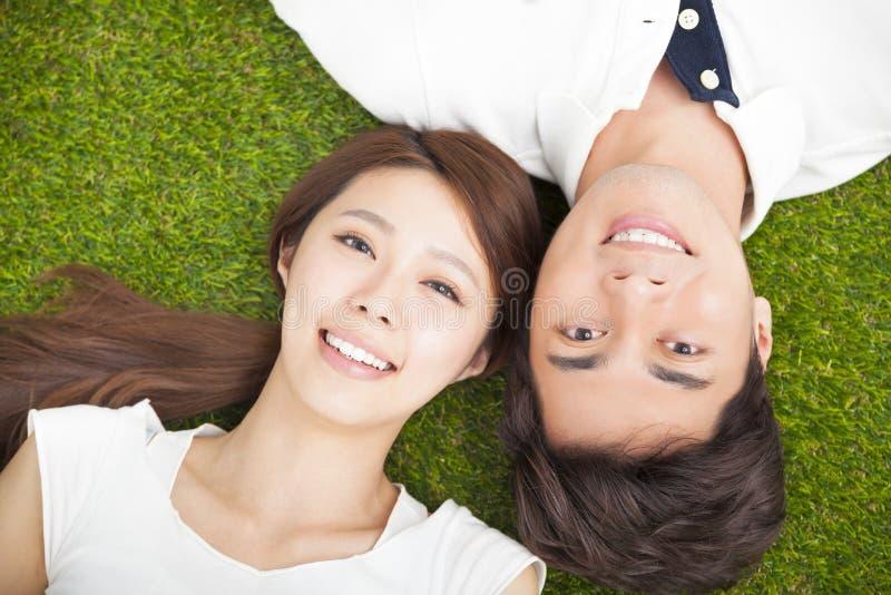 一起说谎在草的年轻夫妇 库存照片