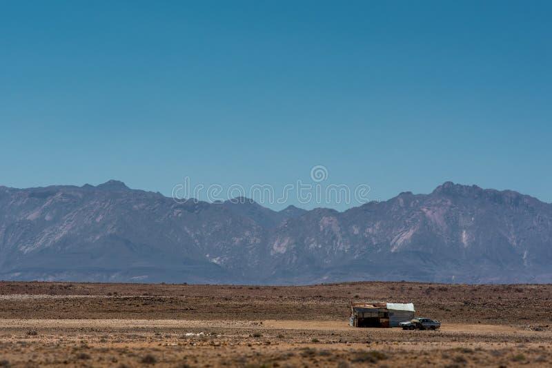 一辆偏僻的棚子和汽车在浩大和干燥纳米比亚风景中,反对布兰德贝格山 库存图片