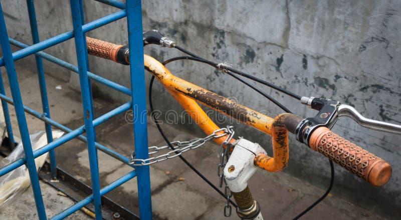 一辆停放的自行车的橙色把手由在雅加达拍的链照片锁了印度尼西亚 库存照片