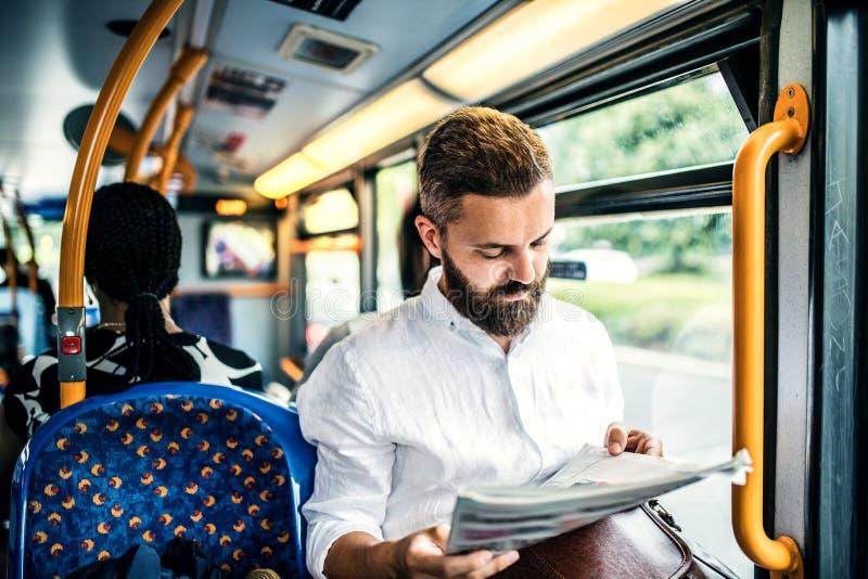 一辆公共汽车的行家人在城市,旅行到工作和读报纸 免版税库存图片