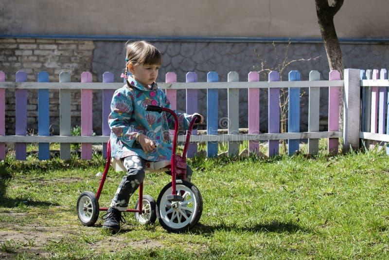 一辆减速火箭的三轮车的小女孩 图库摄影