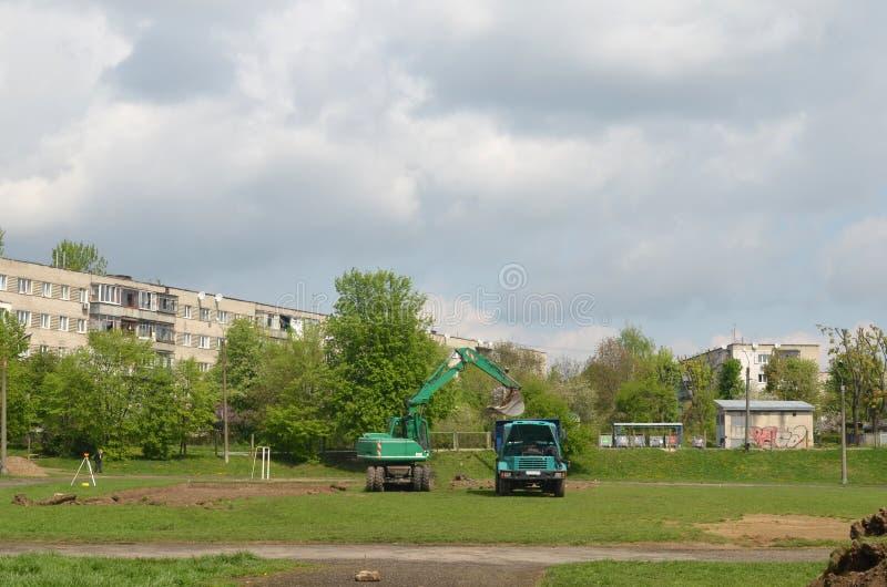 一辆大挖掘机装载的倾销者卡车在体育场内 免版税库存照片