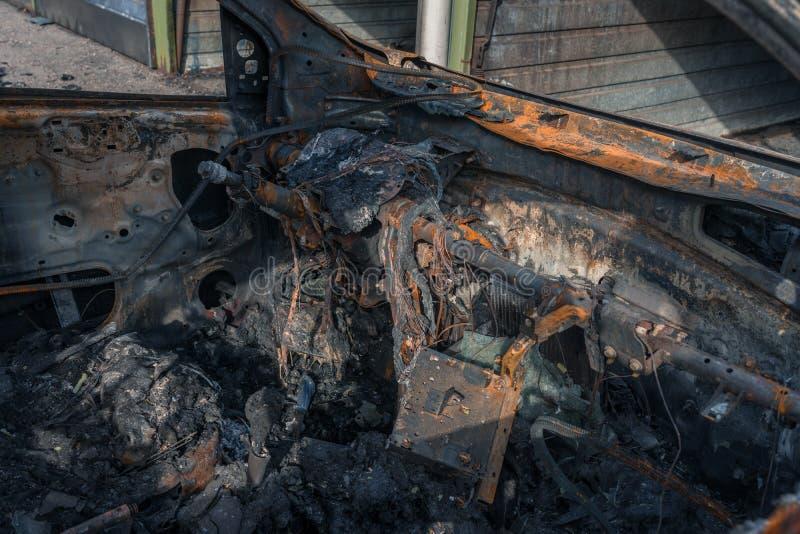 一辆完全地被烧的汽车的内部在郊区 库存照片