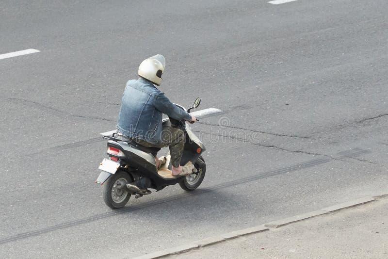 一辆小脚踏车的一个人在城市 免版税库存图片