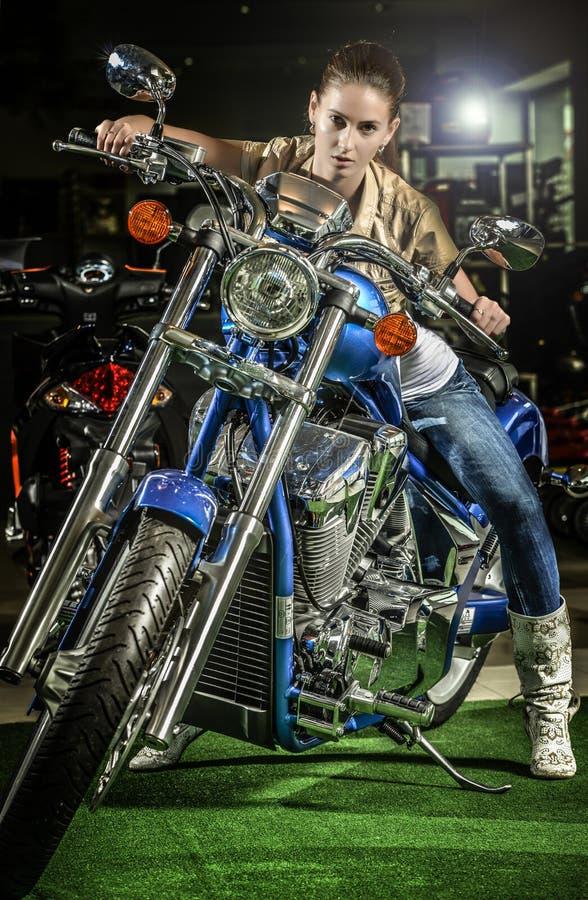 一辆摩托车的印象深刻的妇女在moto展示 库存图片