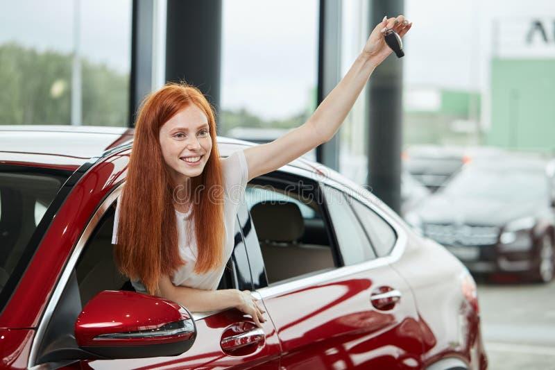 一辆新的汽车惊奇的年轻愉快的妇女对汽车陈列室,从她的丈夫的礼物 免版税库存图片