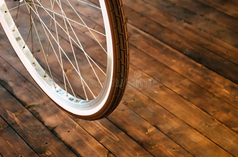 一辆时髦的自行车和在时髦的木背景的一个棕色橡胶轮胎的轮子有一个白色外缘的 免版税库存照片