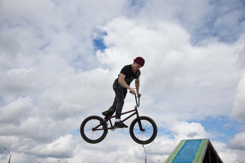 一辆极端自行车的一个少年执行一个复杂的把戏 图库摄影