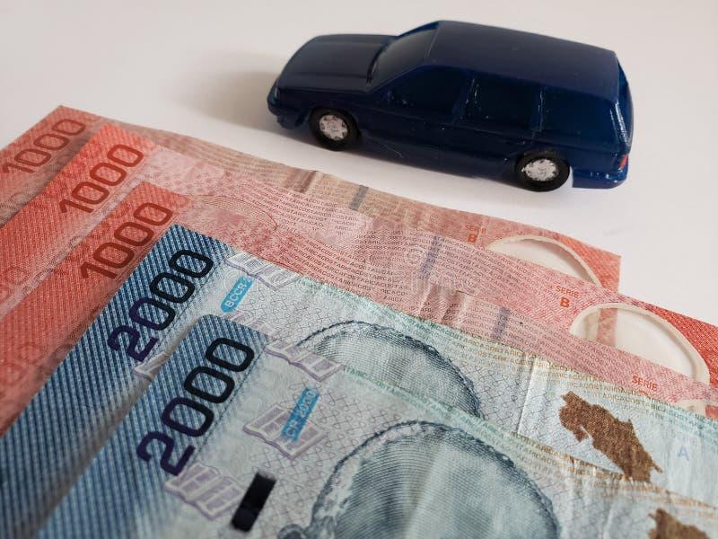一辆汽车的哥斯达黎加的钞票和图在深蓝的 图库摄影