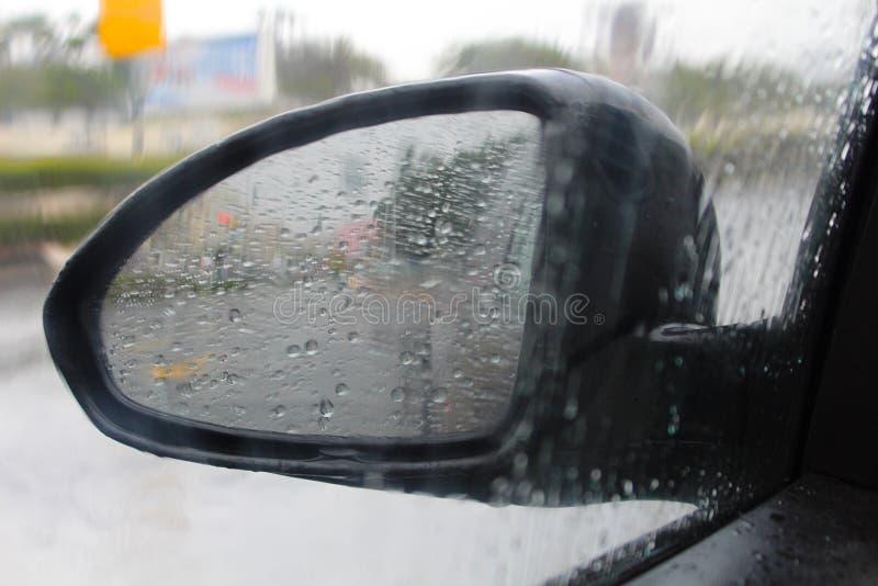 一辆汽车的旁边镜子有雨珠的 冬天天气在以色列,大雨 图库摄影