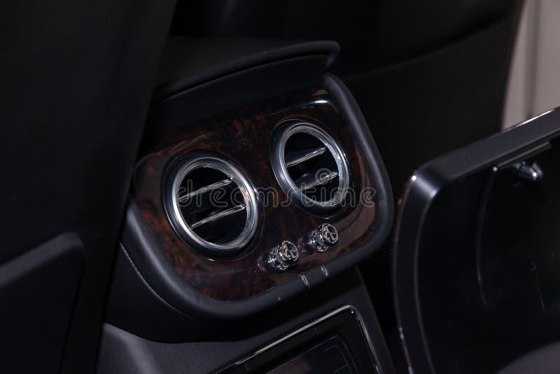 一辆现代豪华汽车的内部的部分的特写镜头视图以两后方中央透气镀铬物回合为目的 库存图片