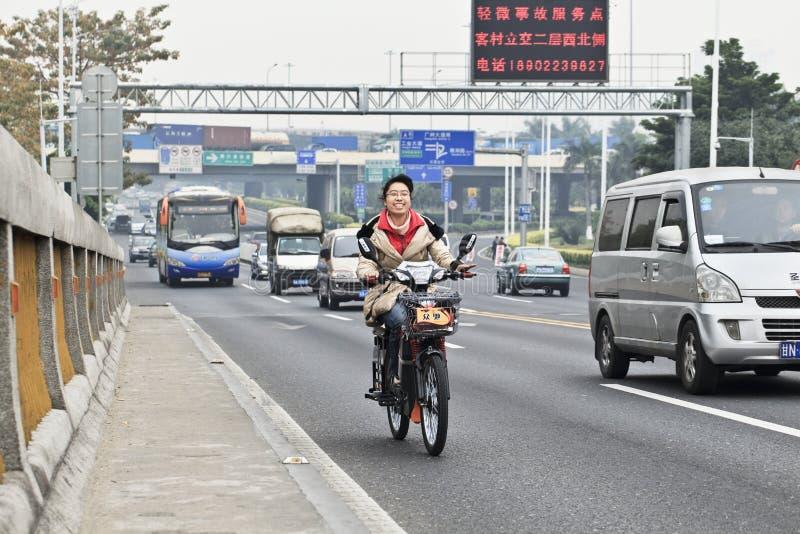 一辆电自行车的快乐的女孩在路,广州,中国 免版税库存图片