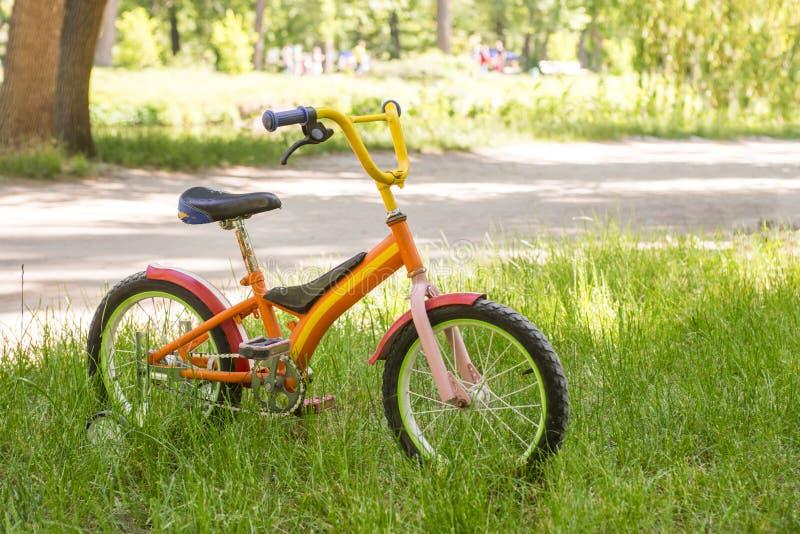 一辆红色儿童自行车在绿草站立 免版税库存图片