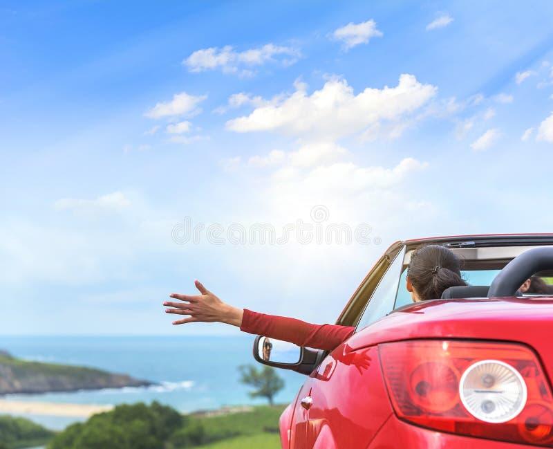 一辆红色敞篷车汽车的女孩 免版税库存照片