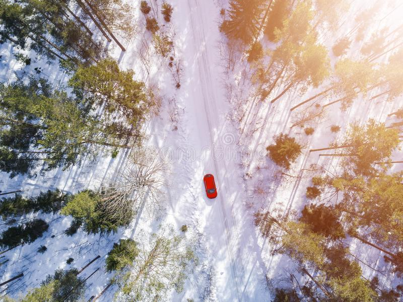 一辆红色汽车的鸟瞰图在白色冬天路的 冬天风景乡下 多雪的森林航拍有一辆红色汽车的 库存照片