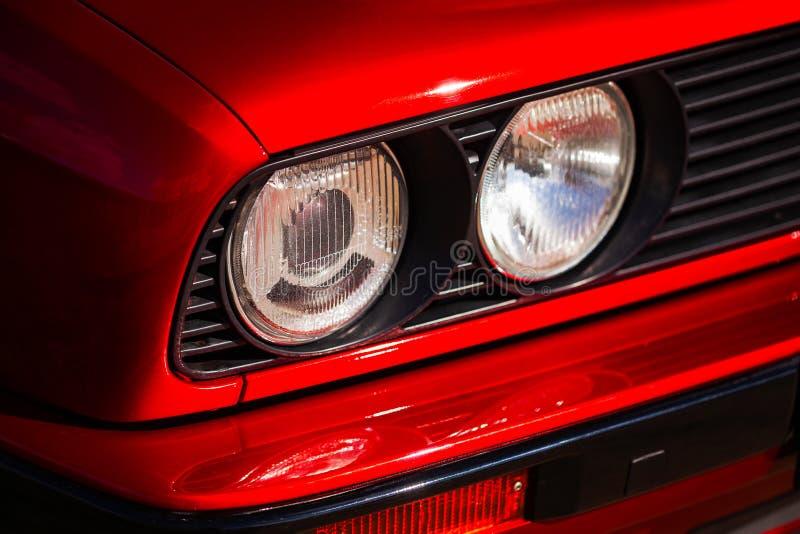 一辆红色,老,减速火箭的汽车,特写镜头的车灯 免版税库存图片