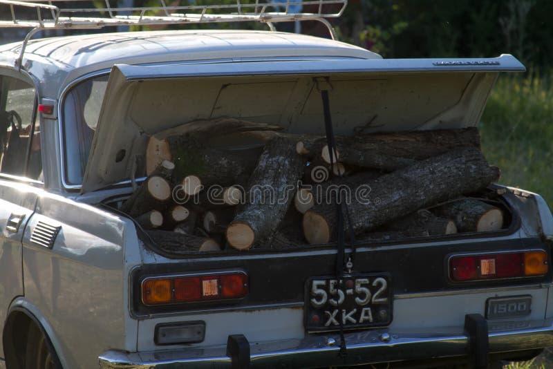 一辆老汽车的照片有充分一根开放树干的篝火或壁炉的木柴 免版税图库摄影