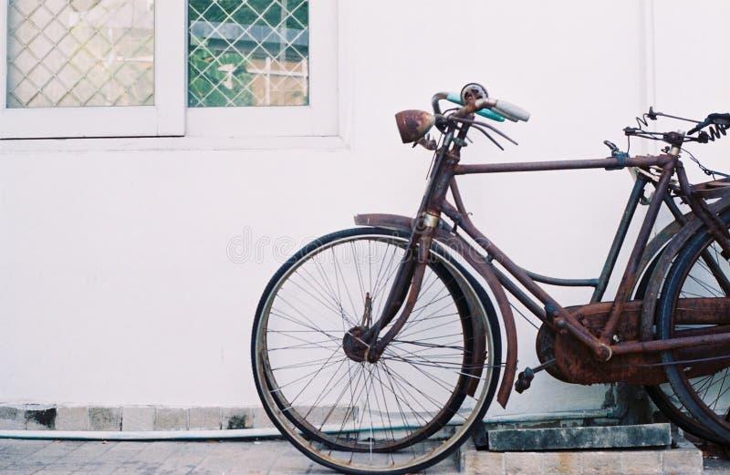 一辆老自行车倾斜对墙壁 免版税库存照片