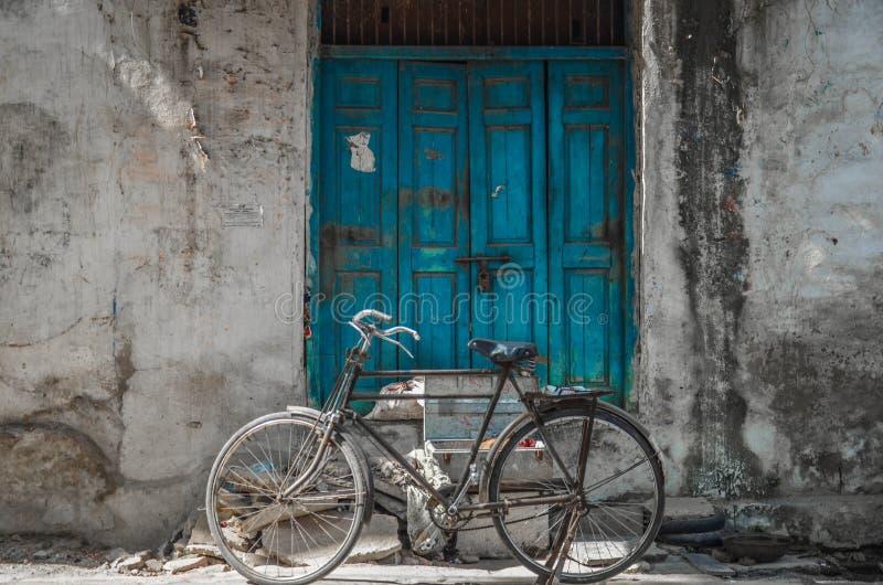 一辆老自行车在一老葡萄酒蓝色木绝密一个老房子前面停放了外面在乔德普尔城,拉贾斯坦,印度 免版税库存图片