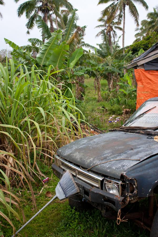 一辆老,生锈和残破的汽车在一个后院在Eua离开在汤加 免版税库存照片