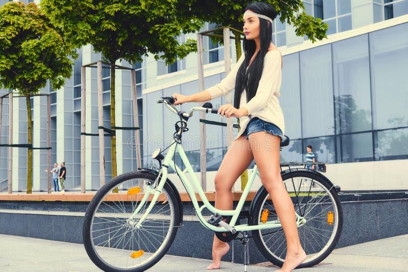 一辆自行车的一名妇女在现代大厦背景 库存照片