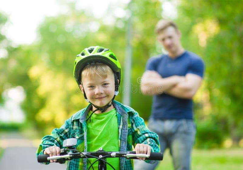 一辆自行车的孩子有父亲的在公园 免版税库存图片