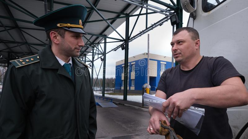 一辆重型卡车的司机与海关检查员沟通在输入问题前的重量控制 免版税图库摄影