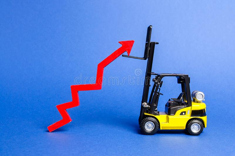 一辆黄色铲车培养一个大红色箭头  在生产率的产业和基础设施的成长和发展 ?? 库存照片