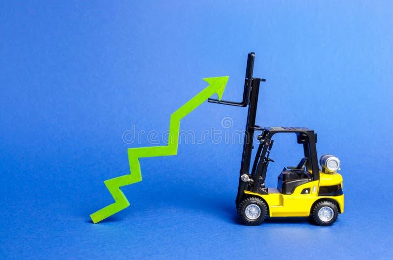 一辆黄色铲车培养一个大绿色箭头  在生产率的产业和基础设施的成长和发展 库存图片
