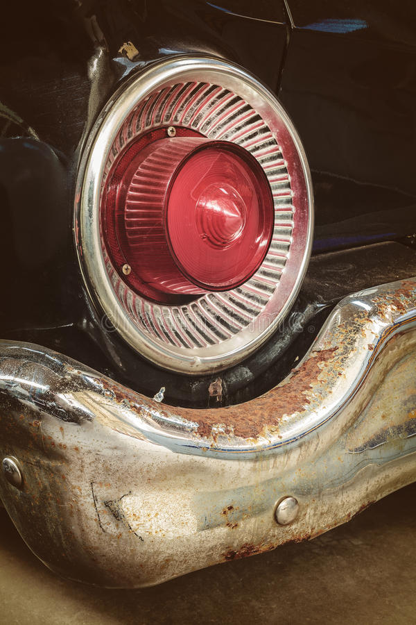 一辆经典汽车的生锈的尾灯和防撞器 免版税库存照片