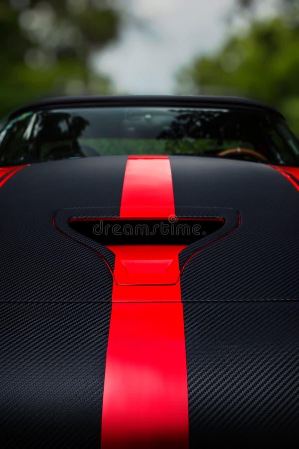 一辆黑暗的赛跑的跑车的细节有帽子瓢出气孔和红色条纹的 免版税图库摄影