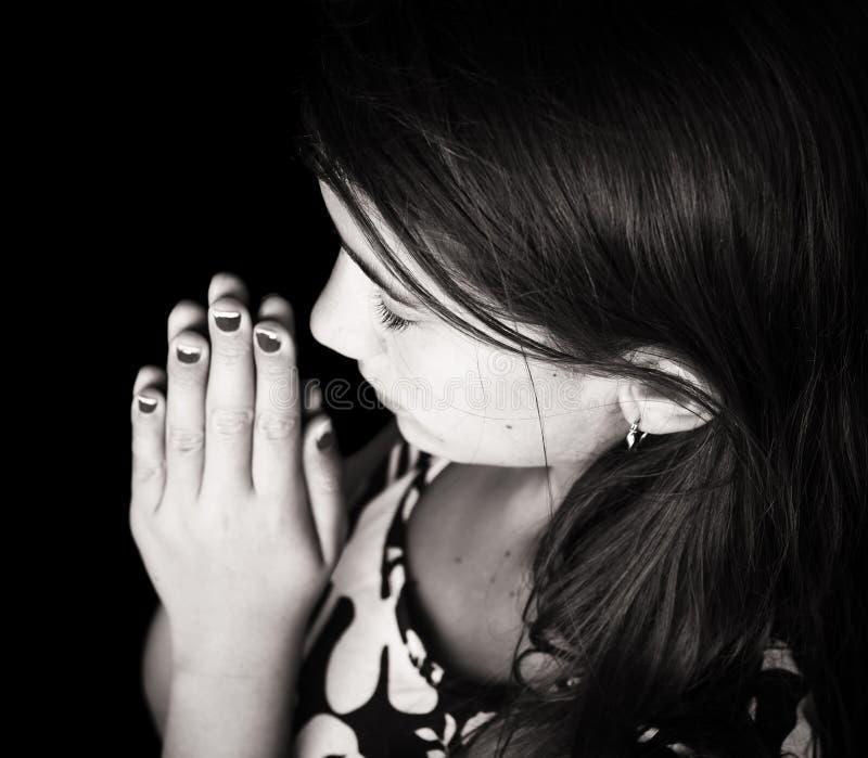 一逗人喜爱女孩祈祷的黑白画象 免版税库存照片