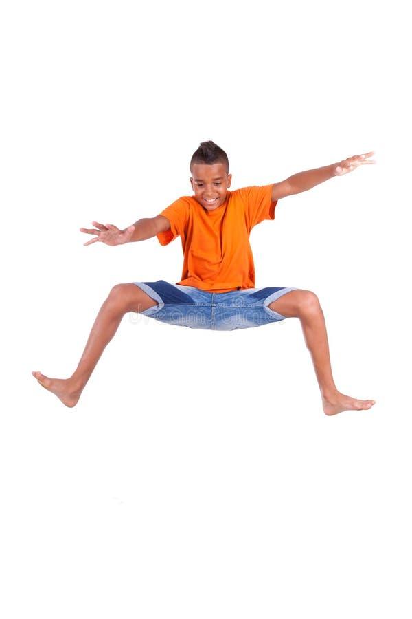 一逗人喜爱少年黑男孩跳跃的画象 库存图片