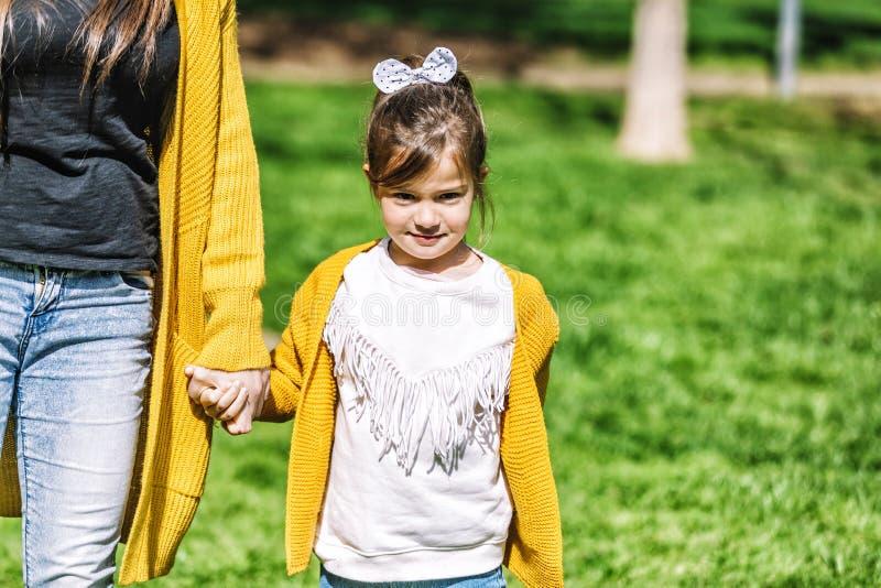 一逗人喜爱的女孩的正面图有一个顶头领带身分在公园和看的照相机,当握有妈妈的手a的时 库存照片