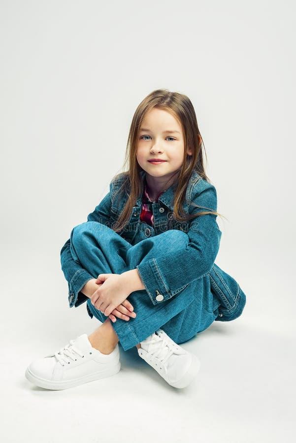 一逗人喜爱的女孩的演播室画象 孩子牛仔布裤子和夹克和白色运动鞋的时尚孩子 免版税库存图片