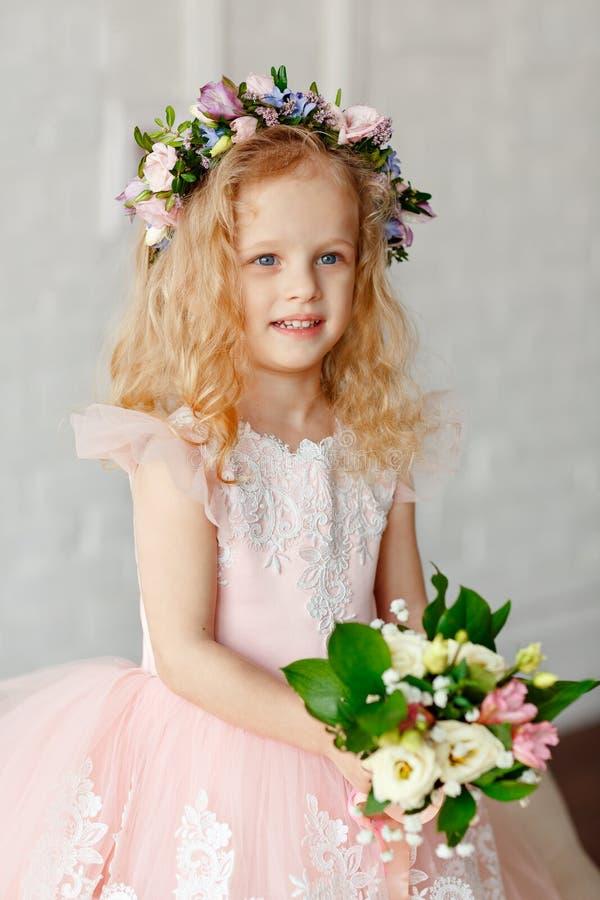 一逗人喜爱的女孩花和一美丽的花束的画象花圈的在一个明亮的演播室 免版税库存图片