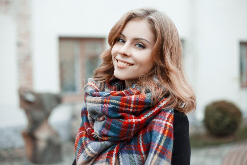 一逗人喜爱的少女的画象有美丽的蓝眼睛的与与卷曲金发的有吸引力的微笑在冬天时髦的衣裳 图库摄影