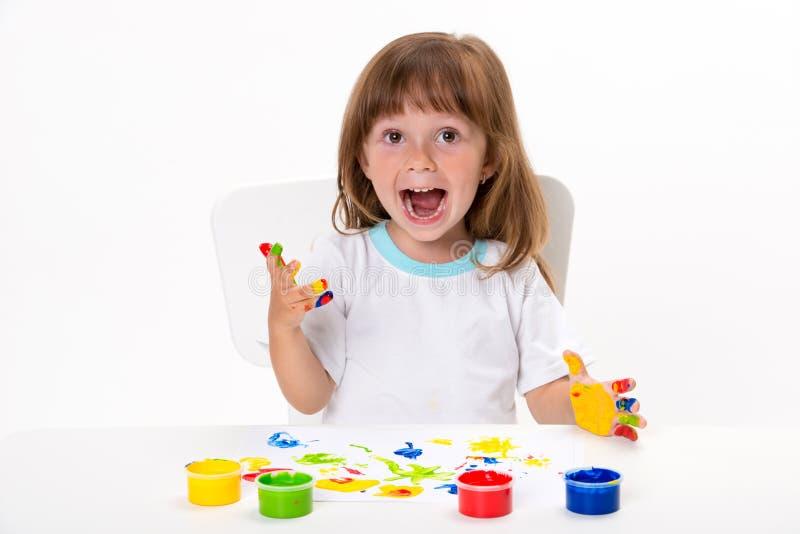 一逗人喜爱的快乐的愉快的微笑的女孩的特写镜头画象画她有在白色隔绝的树胶水彩画颜料或手指油漆的自己的手 免版税库存图片