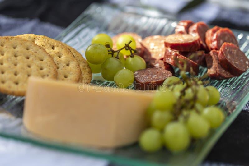 一道鲜美开胃菜用肉、乳酪、薄脆饼干和葡萄 图库摄影