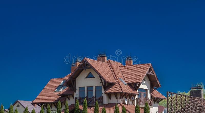 一部分的一个现代砖房子在天空背景的一个铺磁砖的屋顶下 与阳台的村庄 房子楼层二 木房子 居住 免版税库存图片
