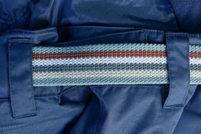 一部分的一条镶边传送带由布料制成在蓝色裤子 免版税图库摄影