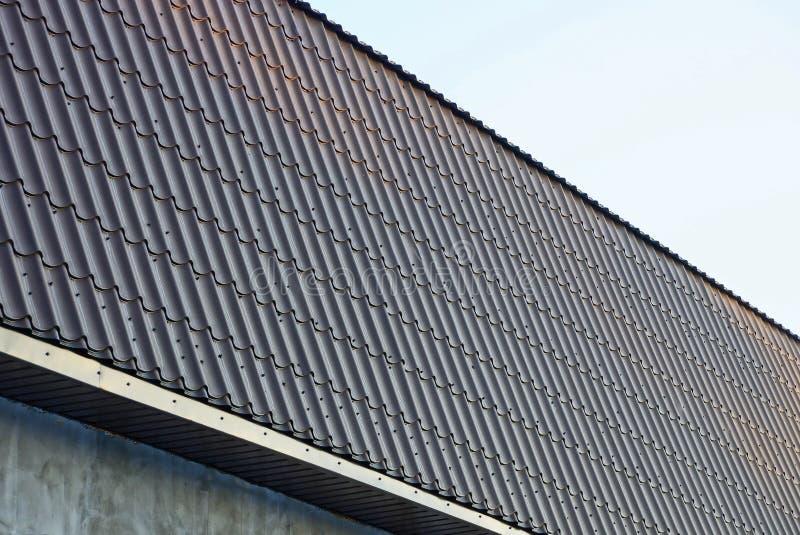 一部分的与一个长的屋顶的一个大厦在棕色铺磁砖的瓦片下 库存照片