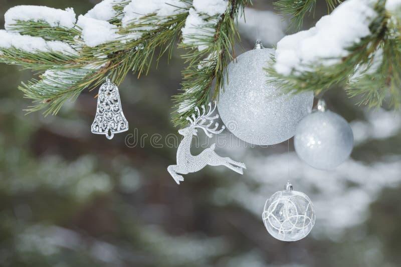 一部分的与动物圣诞老人的驯鹿装饰品和银中看不中用的物品的装饰的圣诞树在多雪的分支 库存图片