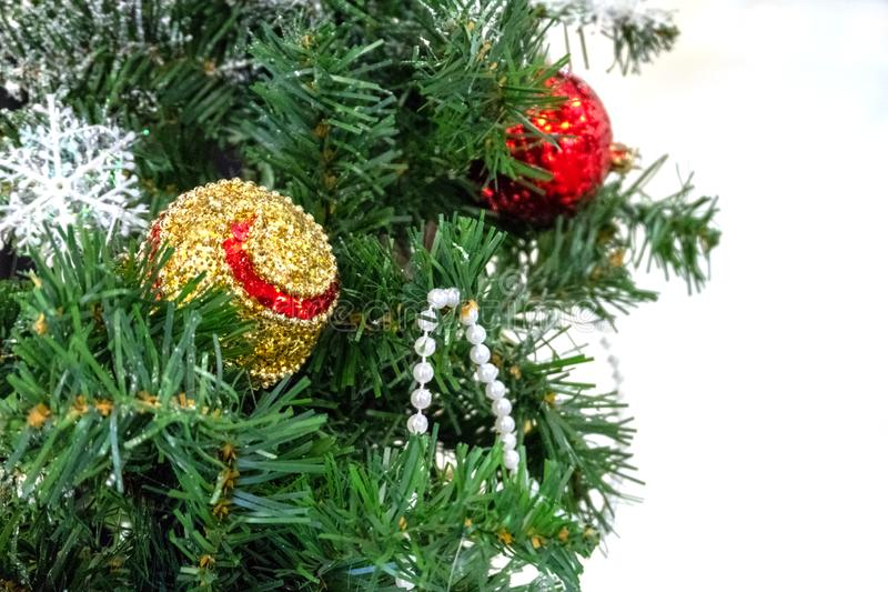 一部分的与发光的球的一棵绿色圣诞树在白色背景 圣诞节装饰、玩具、雪花和小珠 室 库存照片
