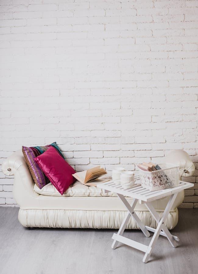 一部分的与长沙发和装饰枕头,与书的白色木桌的内部对此 免版税库存照片