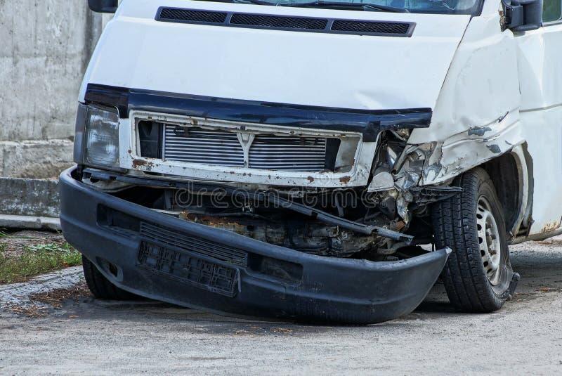 一部分的在事故以后的白色公共汽车与一个残破的防撞器和车灯在路 库存照片