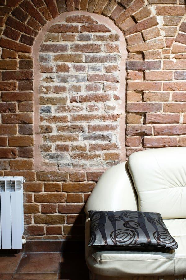 一部分的在古老房子的红砖墙壁的背景的白色沙发 时尚和样式的概念 库存照片