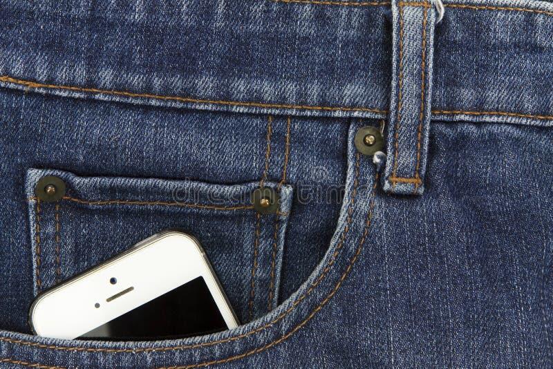 一部分的在蓝色牛仔布的前面口袋的流动白色手机 免版税库存照片
