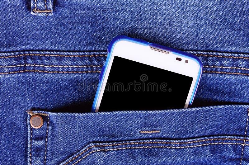一部分的在蓝色牛仔裤口袋的手机 库存图片